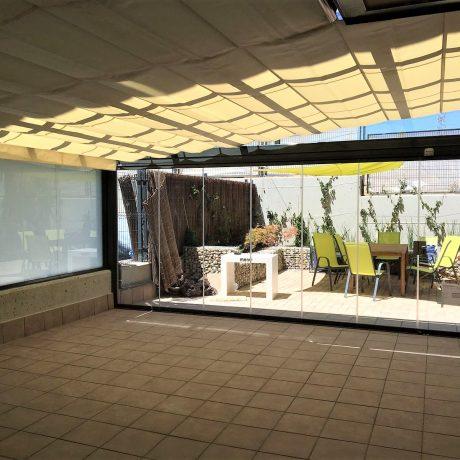 Toldo garden bajo techo de cristal