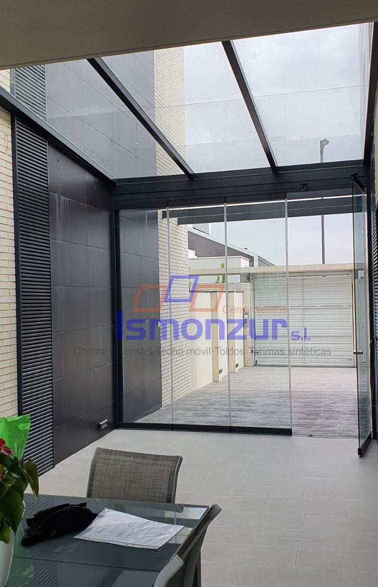 Cortinas correderas de cristal y techo móvil en terraza
